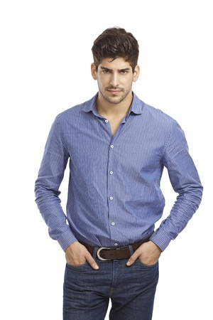 unsmiling: Confident young man standing in jeans and shirt with hands in pocket. Looking at camera.
