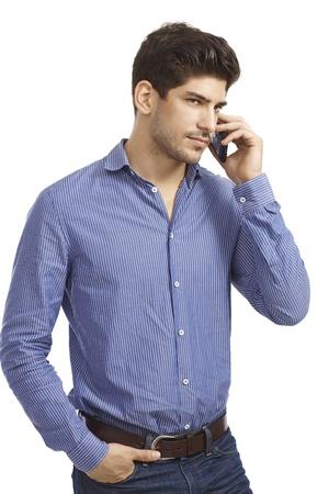 llamando: Hombre joven hablando por el m�vil, mirando a otro lado, la mano en el bolsillo.