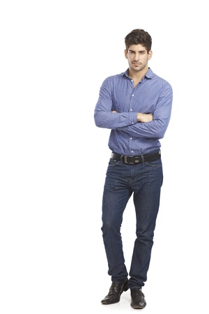 full size: Confident young man in jeans and shirt standing arms crossed.
