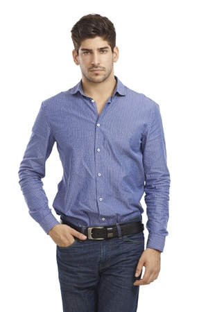 bristly: Portrait of young man standing in jeans and shirt, hand in pocket. Stock Photo
