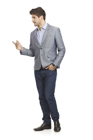 full size: Young businessman talking to someone, turning right, gesturing other hand in pocket.