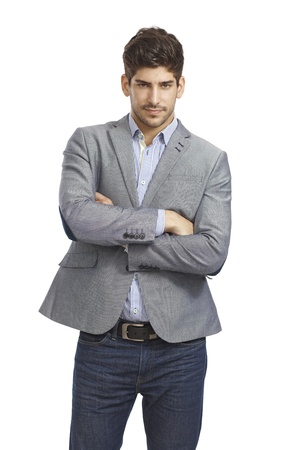 bristly: Portrait of confident young businessman standing arms crossed, looking at camera.