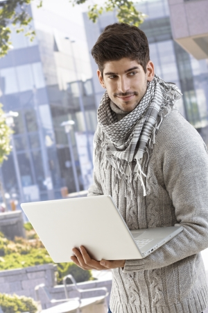 Handsome young man using laptop computer outdoors, smiling. photo
