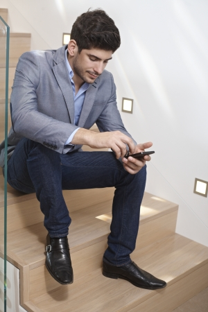 Young man sitting on stairs at home, using mobile phone. photo