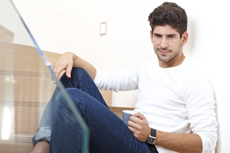 Handsome young man sitting on stairs at home drinking coffee, looking at camera. Stock Photo - 17420582