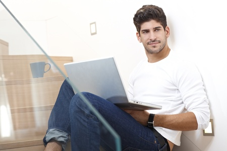 bristly: Happy young man sitting in stairway at home, using laptop computer, smiling, looking away.