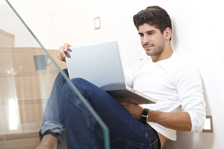 Smiling young man using laptop computer at home, sitting on stairs. Stock Photo - 17420581