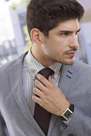 Serious young businessman adjusting tie, looking away. Stock Photo - 17420356