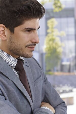 bristly: Profile of confident young elegant businessman smiling.