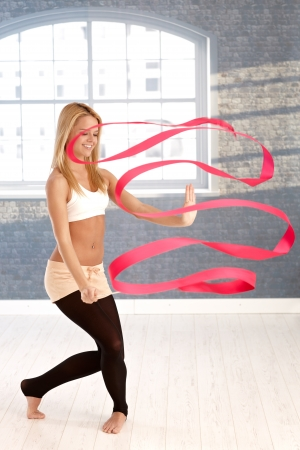 Young female rhytmic gymnast exercising with ribbon. Stock Photo - 17505853