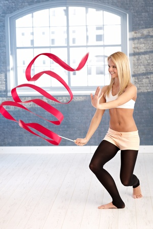 gymnastics equipment: Happy young rhytmic gymnast exercising with ribbon. Stock Photo
