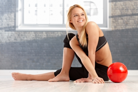 Pretty female dancer stretching, sitting on floor, having ball, smiling happy. Stock Photo - 17505854