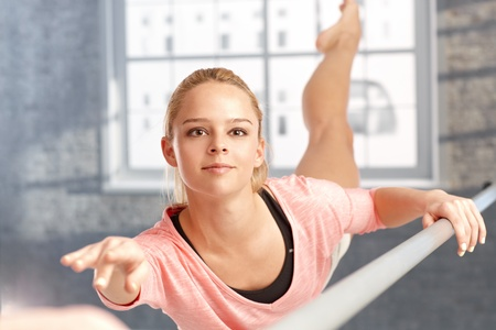Beautiful young female dancer practicing, lifting leg high. Stock Photo - 17505835