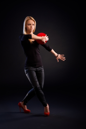 Pretty young woman in black outfit exercising with ball over black background. photo