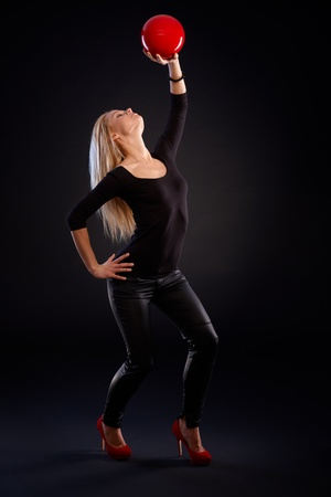 Artistic photo of pretty female dancer holding ball in passionate pose. photo