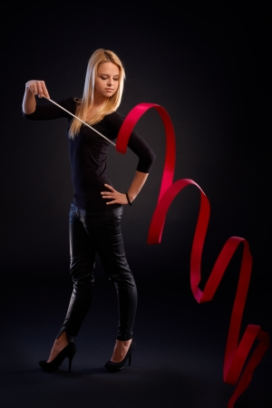 Artistic photo of young rhytmic gymnast exercising with ribbon over black background. photo