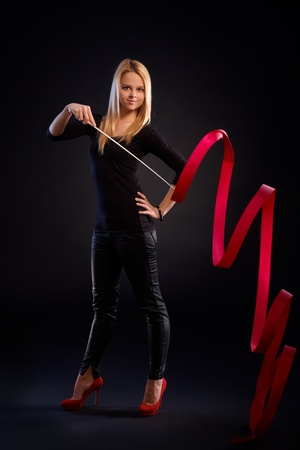 Pretty rhytmic gymnast exercising with ribbon over black background. photo