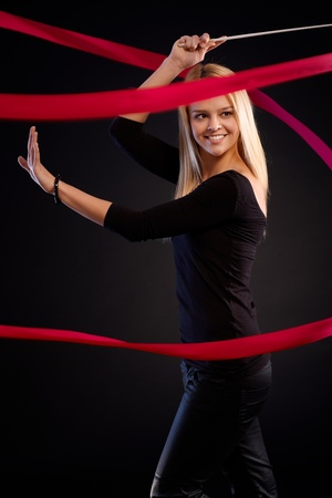 Beautiful female dancer using ribbon, smiling happy over black background. photo