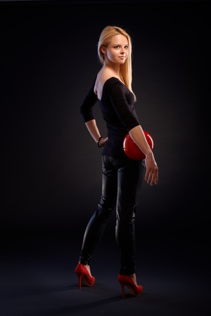 Pretty girl standing in black outfit, holding red ball, looking away over black background. photo