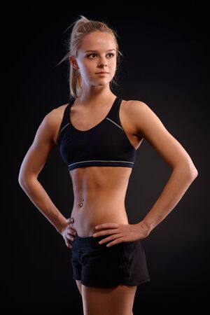 Attractive young athletic girl in sportswear standing with hands on hip, looking away. Black background. photo