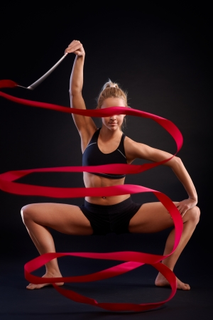 Artistic photo of young rhytmic gymnast doing ribbon exercise over black background. photo