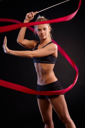 Pretty rhytmic gymnast girl exercising with ribbon over black background. photo