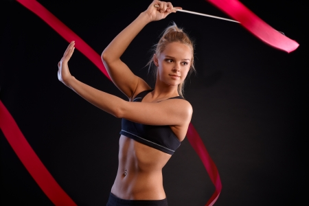 Artistic photo of pretty gymnast girl exercising with ribbon, looking away. Black background. photo