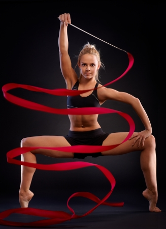 Rhytmic gymnast in a beautiful pose using ribbon over black background. photo