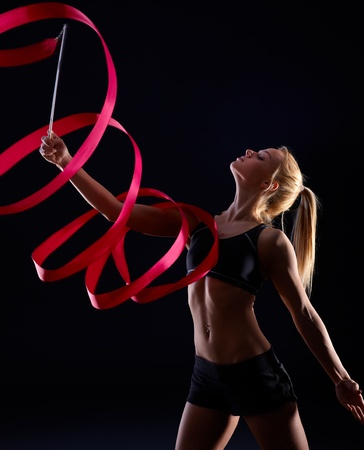 gymnastics equipment: Artistic photo of pretty female dancer using ribbon, exercising over black background.