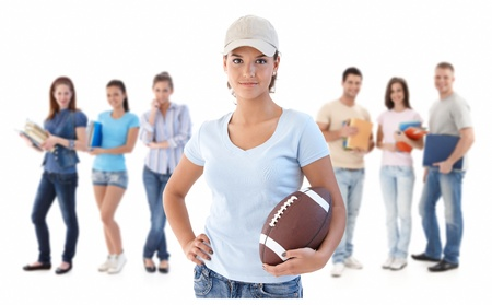 Group of happy young people, smiling woman at front holding football, isolated on white background. photo