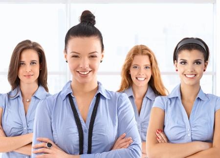 uniformes de oficina: Equipo retrato de atractivas jóvenes trabajadoras frente a la oficina de uniforme azul, mirando a cámara, sonriendo. Foto de archivo
