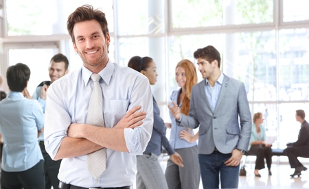 arms crossed: Portrait of happy young businessman standing in office lobby, people talking in background. Stock Photo
