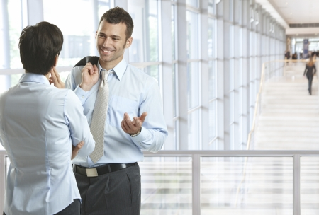 corporate image: Business people talking in office lobby, smiling. Plenty of copyspace. Stock Photo