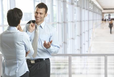 dos personas hablando: Los hombres de negocios hablando en vestíbulo de la oficina, sonriendo. Un montón de copyspace.
