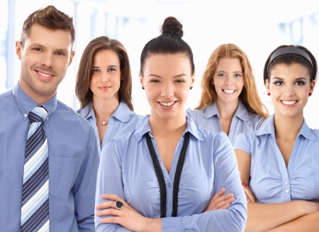 white color worker: Team portrait of happy office workers wearing uniform, looking at camera smiling. Stock Photo