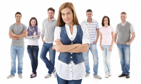 Portrait de groupe de jeunes gens heureux ensemble, regardant la caméra en souriant. Jeune femme à l'avant.