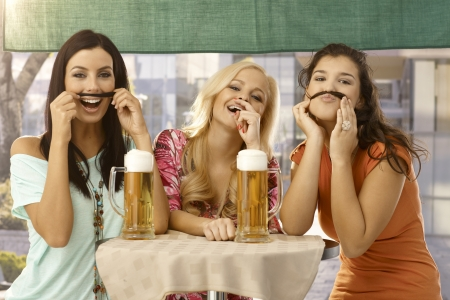 horizontal bar: Pretty girls having fun, forming moustache from hair, drinking beer in outdoor bar, smiling. Stock Photo