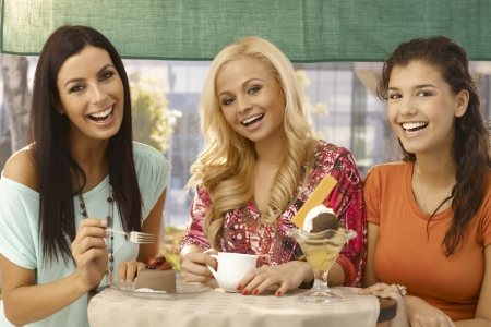 woman eating cake: Pretty young female friends having cake and ice cream at outdoor cafe, smiling happy. Stock Photo