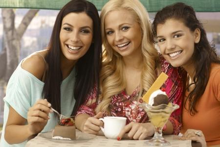 Portret van drie mooie vrouwelijke vrienden glimlachend gelukkig, met snoepjes. Stockfoto