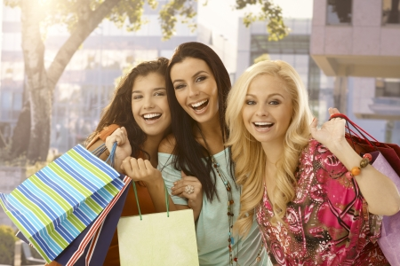 Portrait of shopaholic female friends smiling happy with shopping bags. photo