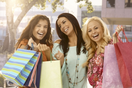 Attractive female friends holding shopping bags, smiling happy outdoors. photo