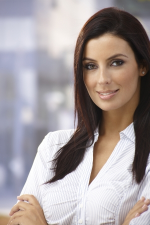 pretty woman face: Outdoor portrait of confident young woman smiling arms crossed.