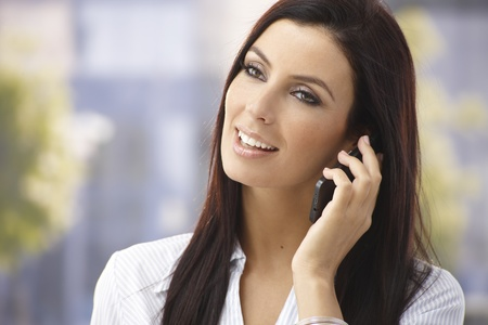 Happy woman talking on mobilephone, smiling outdoors. Stock Photo - 17926754