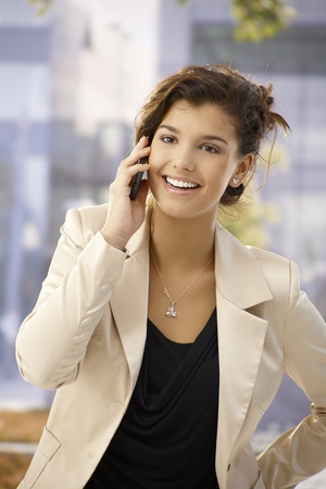 Beautiful young businesswoman talking on mobilephone outdoors, smiling happy. photo