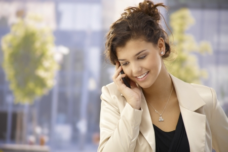 calling communication: Pretty young woman talking on mobilephone outdoors, smiling happy.