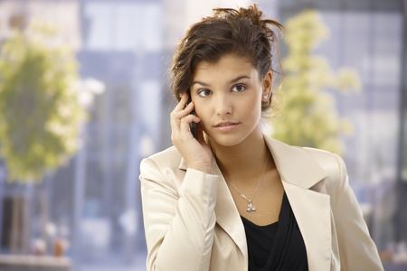 Outdoor portrait of pretty businesswoman talking on mobilephone. photo