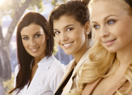 Closeup portrait of attractive young businesswomen outdoors, smiling happy. Selective focus. photo