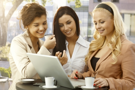 Pretty young businesswomen standing in outdoor cafe, using laptop computer, smiling happy. photo