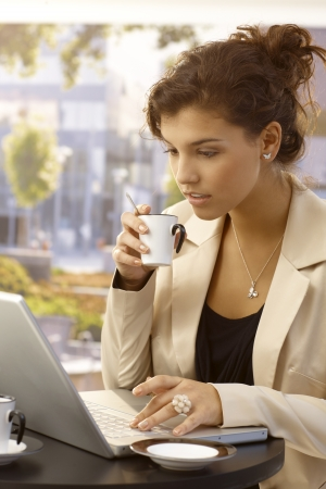 Attractive young businesswoman using laptop and drinking coffee outdoors. photo