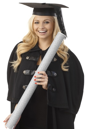 Happy female graduate in academic dress holding diploma, smiling. photo